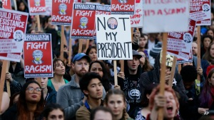 Protesters hold signs during a protest against the election of President-elect Donald Trump, Wednesday, Nov. 9, 2016, in downtown Seattle. (AP Photo/Ted S. Warren)